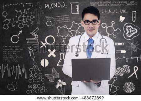 Male doctor holding a laptop on blackboard background