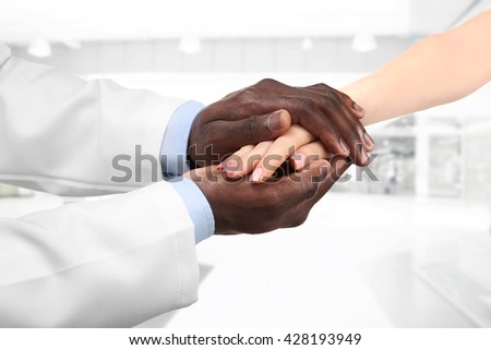 Male doctor holding patient's hand, on blurred background - stock photo