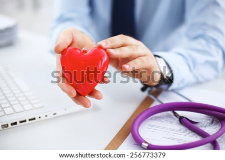 Male doctor holding red heart while using laptop at desk in clinic - stock photo
