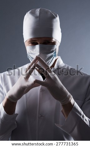 Male doctor in cap and mask wear rubber medical gloves in contrasting light. - stock photo
