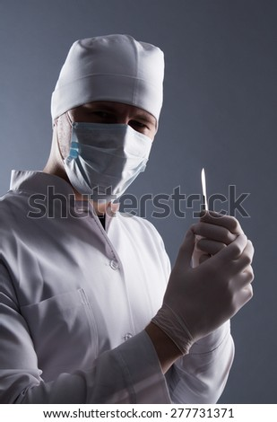 Male doctor in cap, mask and rubber medical gloves holding scalpel. - stock photo