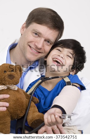 Male doctor in early forties holding five year old disabled patient during office visit - stock photo