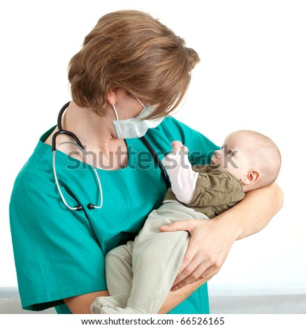 male doctor in green uniform and protective medical mask examining baby boy - stock photo