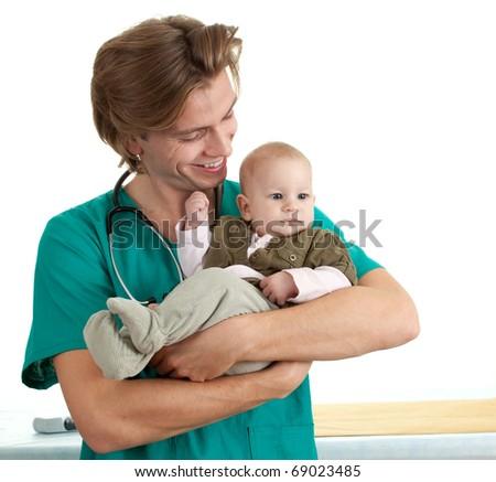 male doctor in green uniform examining baby boy - stock photo