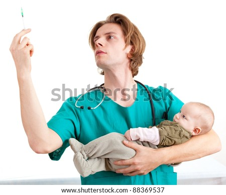male doctor in green uniform examining baby boy, white background - stock photo