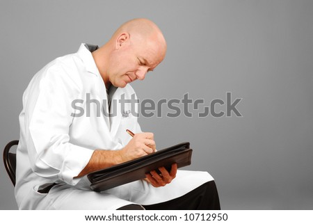 Male doctor in white coat looking serious while making notes - stock photo