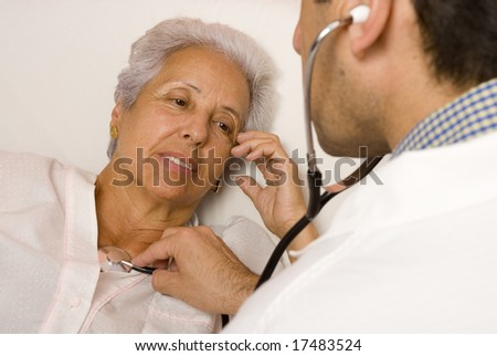 Male doctor listening with stethoscope to senior patient's heart and lungs