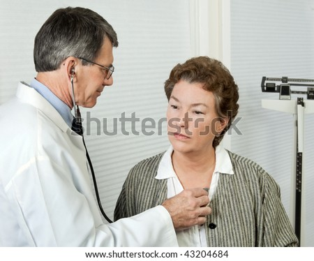 Male doctor listens to mature woman's heart during an office visit.