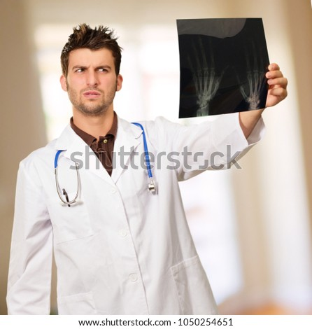Male Doctor Looking At X-ray, Indoors