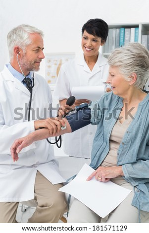Male doctor measuring blood pressure of a senior patient in the medical office - stock photo