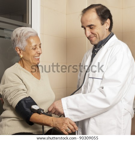 Male doctor measuring blood pressure of senior female patient at hospital