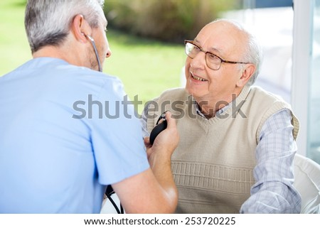 Male doctor measuring blood pressure of senior man at nursing home porch - stock photo