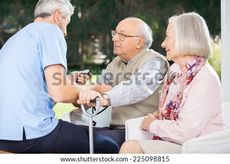 Male doctor measuring blood pressure of senior man while woman looking at them at nursing home - stock photo