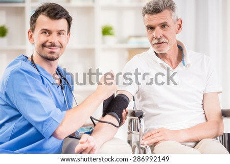 Male doctor measuring blood pressure to older patient sitting at wheelchair. - stock photo