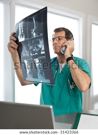 Male doctor on the phone in a hospital or office clinic, examining spinal scans and discussing his findings. - stock photo