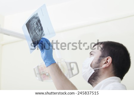 Male doctor or dentist looking at x-ray - stock photo