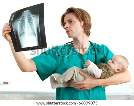 male doctor reading chest x-ray and examining baby boy - stock photo