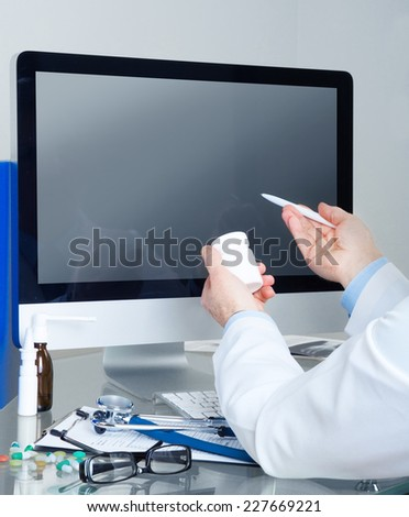 Male doctor show something in computer display