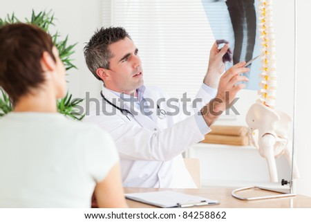 Male Doctor showing a patient a x-ray in a room - stock photo