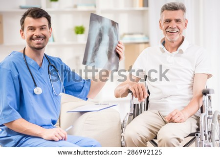 Male doctor showing diagnosis of x-ray image to older patient sitting at wheelchair. - stock photo