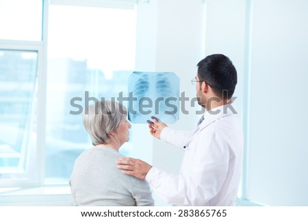 Male doctor showing x-ray to his patient in hospital - stock photo