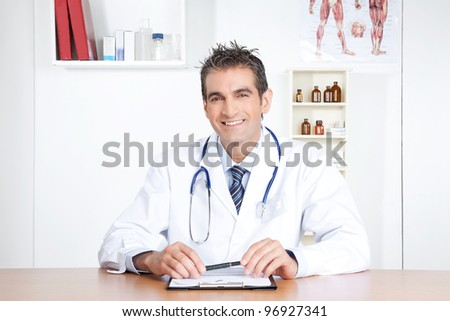 Male doctor sitting at desk with clipboard and pen.
