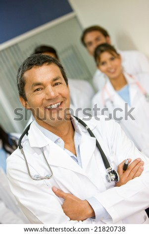 male doctor smiling with his team behind in a hospital