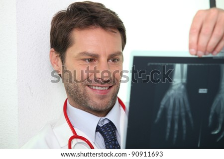 Male doctor stood smiling whilst examining x-ray image - stock photo