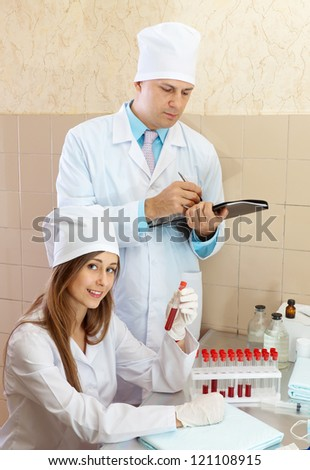 Male doctor supervises the young nurse in medical lab