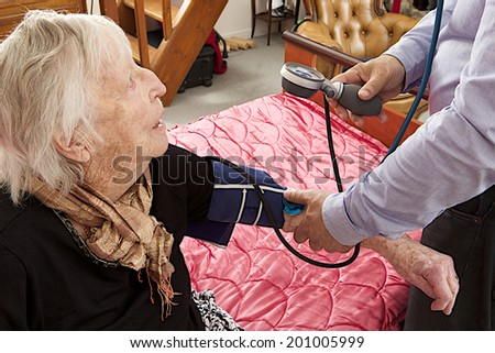 Male doctor taking the pulse of an older woman  - stock photo
