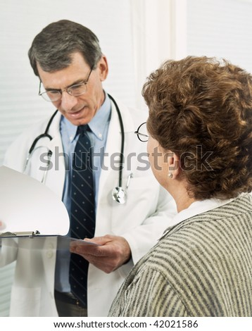 Male doctor talking with female patient. Patient is in sharp focus in the foreground with doctor blurred with background. - stock photo