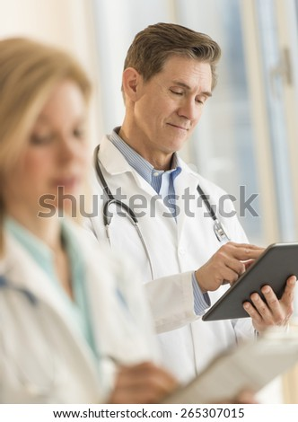 Male doctor using digital tablet with female colleague holding clipboard in foreground at hospital - stock photo