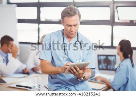 Male doctor using tablet in conference room and colleagues discussing in background