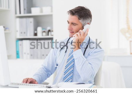 Male doctor using telephone while working on computer at table in clinic - stock photo