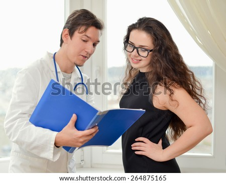 Male doctor with folder and patient standing near window  - stock photo