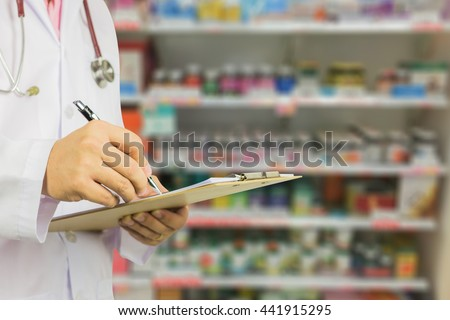 male doctor with stethoscope holding clipboard and writing a prescription,pharmacist writing on prescription clipboard at the hospital pharmacy,Healthcare and medical concept,selective focus - stock photo