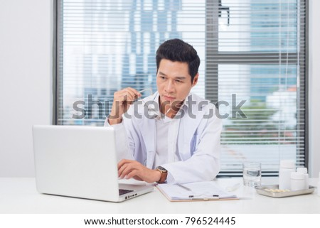 Male doctor working at desk in doctor's room