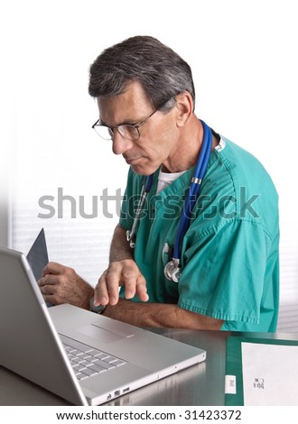 Male Doctor working at his laptop. White background. Closeup