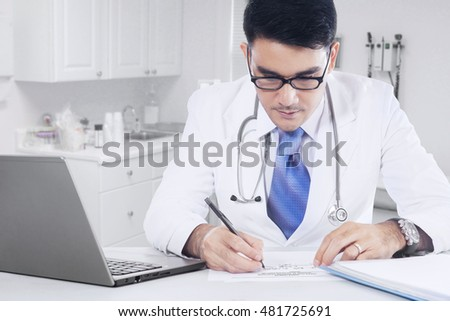 Male doctor working in the clinic and making a medicine recipe with laptop on the table