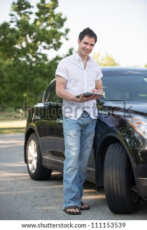 Male Driver Holding a Touch Pad Tablet PC by Car at Road Side - stock photo