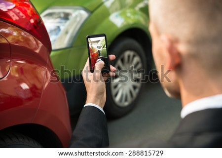 Male Driver Photographing With His Cellphone After Traffic Collision - stock photo