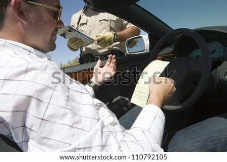 Male driver reading ticket with policeman standing by his car - stock photo