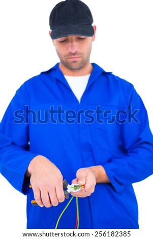 Male electrician cutting wire with pliers over white background - stock photo