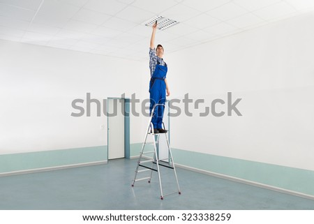Male Electrician On Stepladder Installing Ceiling Light - stock photo