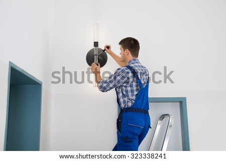 Male Electrician Standing On Stepladder Repairing Light - stock photo