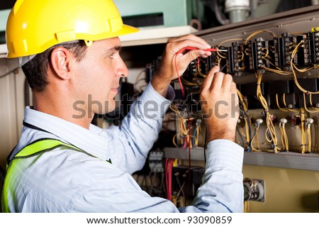 male electrician testing industrial machine - stock photo