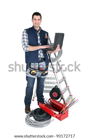 Male electrician with a laptop - stock photo