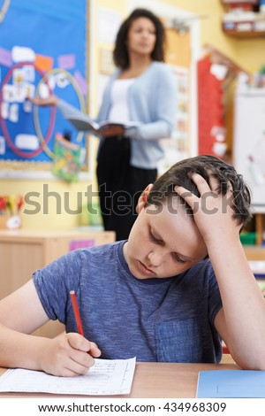 Male Elementary School Pupil Struggling In Class - stock photo