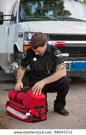 Male emergency medical services professional (EMS) with portable oxygen unit near ambulance - stock photo