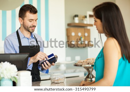 Male employee in a cake shop swiping a credit card in a bank terminal at the cash register in front of a customer - stock photo